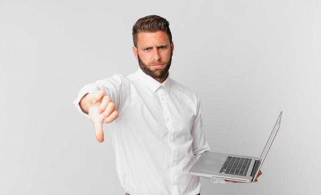 Jonge knappe man die zich boos voelt, duimen naar beneden laat zien en een laptop vasthoudt