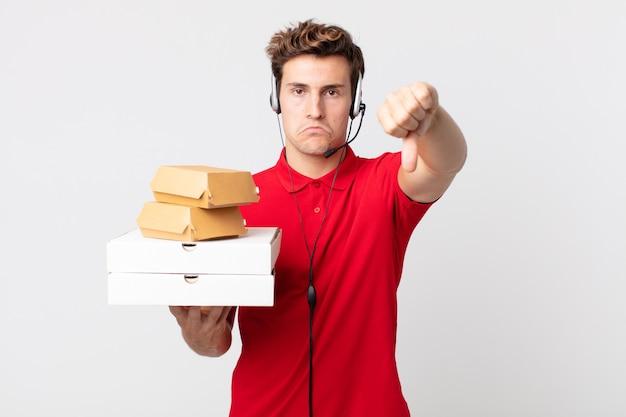 Jonge knappe man die zich boos voelt en duimen naar beneden laat zien. afhaal fastfood concept