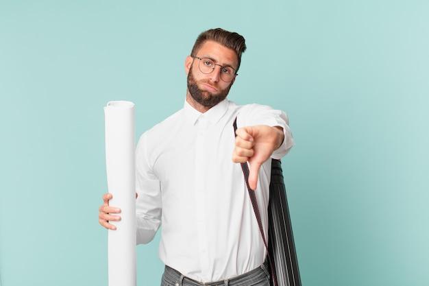 Jonge knappe man die zich boos voelt en duimen naar beneden laat zien. architect concept
