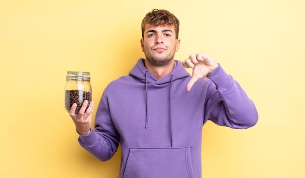 Jonge knappe man die zich boos voelt en duimen naar beneden laat zien. koffiebonen concept