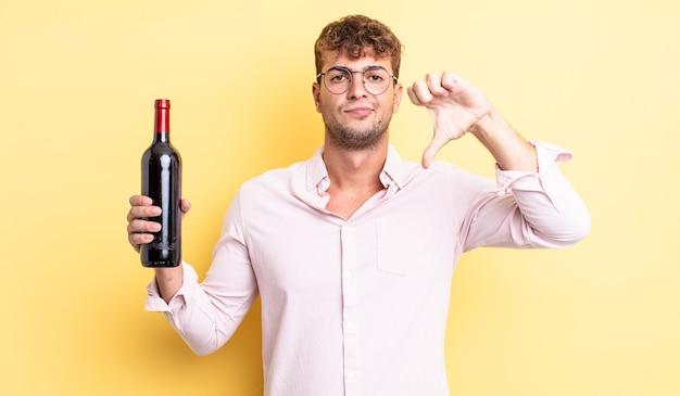 Jonge knappe man die zich boos voelt en duimen naar beneden laat zien. wijnfles concept