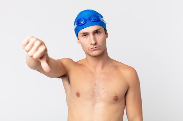Jonge knappe man die zich boos voelt en duimen naar beneden laat zien. zwemmer concept