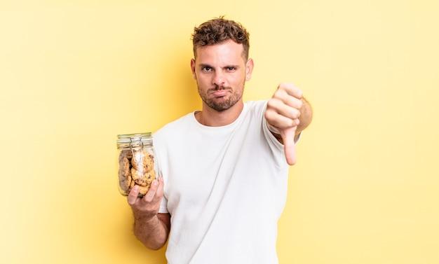 Jonge knappe man die zich boos voelt, met duimen naar beneden, het concept van de koekjesfles