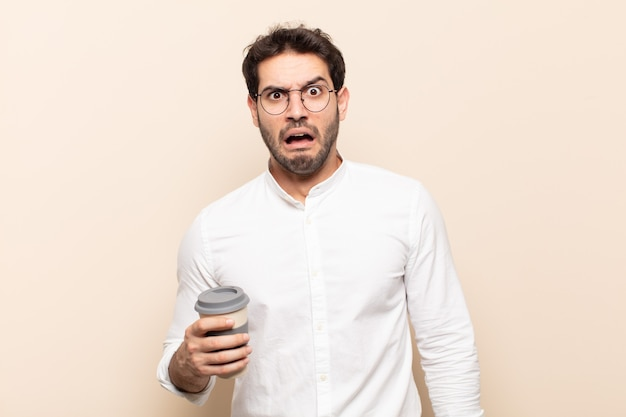 Jonge knappe man die zich doodsbang en geschokt voelt, met zijn mond wijd open van verbazing