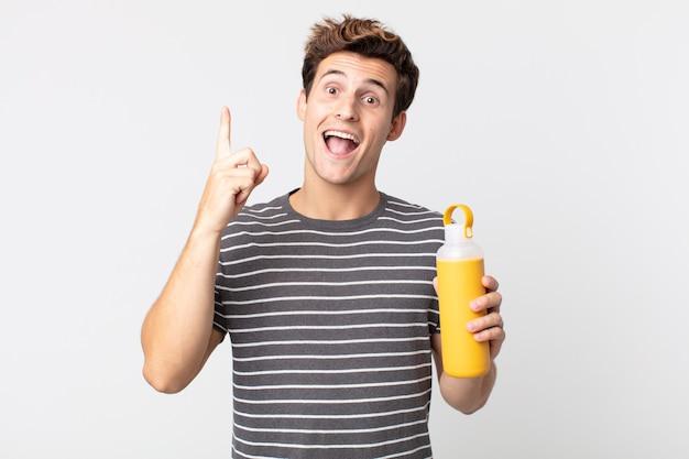 Jonge knappe man die zich een gelukkig en opgewonden genie voelt na het realiseren van een idee en het vasthouden van een koffiethermos