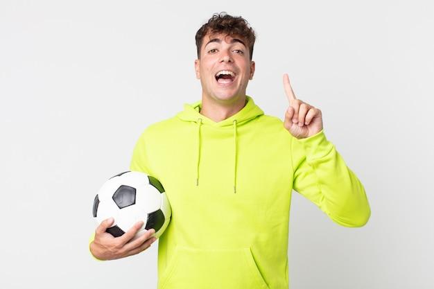 Jonge knappe man die zich een gelukkig en opgewonden genie voelt na het realiseren van een idee en het vasthouden van een voetbal