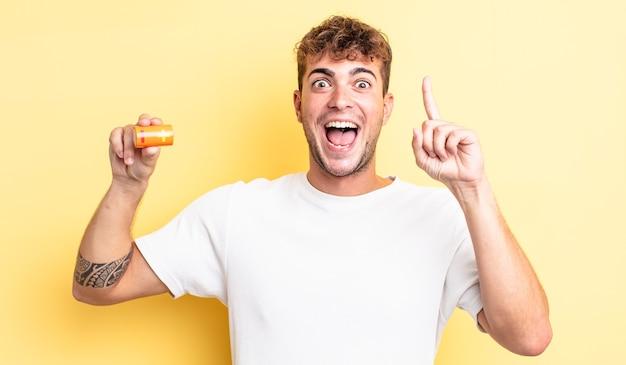 Jonge knappe man die zich een gelukkig en opgewonden genie voelt na het realiseren van een idee met een batterij