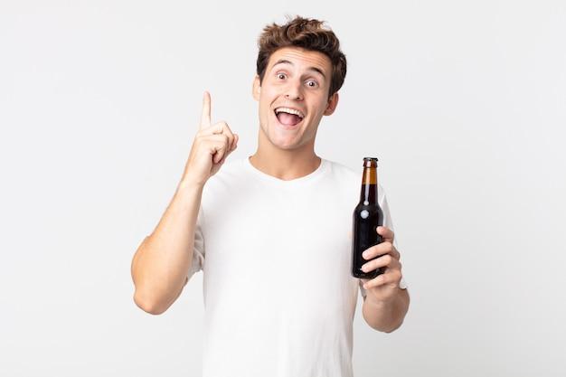 Jonge knappe man die zich een gelukkig en opgewonden genie voelt nadat hij een idee heeft gerealiseerd en een bierflesje vasthoudt