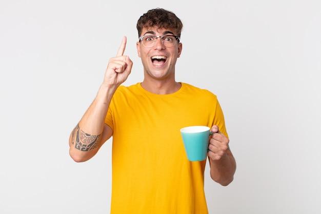 Jonge knappe man die zich een gelukkig en opgewonden genie voelt nadat hij een idee heeft gerealiseerd en een kopje koffie vasthoudt