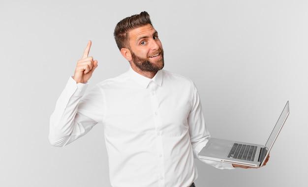 Jonge knappe man die zich een gelukkig en opgewonden genie voelt nadat hij een idee heeft gerealiseerd en een laptop vasthoudt