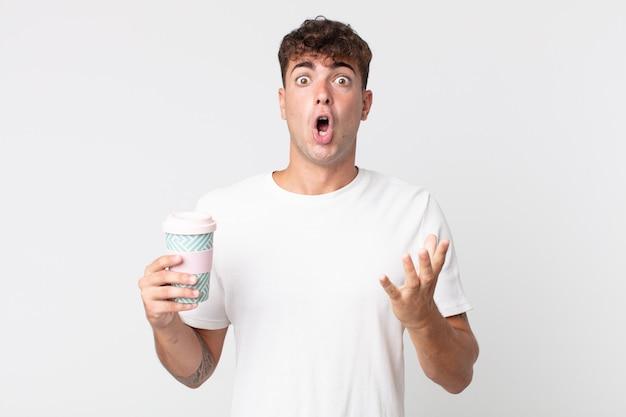 Jonge knappe man die zich extreem geschokt en verrast voelt en een afhaalkoffie vasthoudt