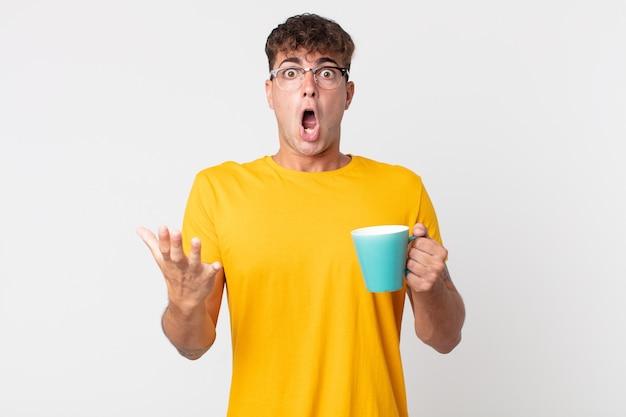 Jonge knappe man die zich extreem geschokt en verrast voelt en een kopje koffie vasthoudt