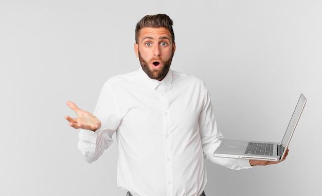 Jonge knappe man die zich extreem geschokt en verrast voelt en een laptop vasthoudt