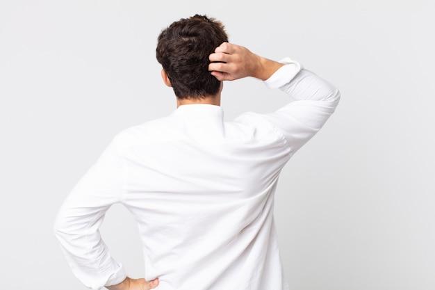 Jonge knappe man die zich geen idee en verward voelt, een oplossing denkt, met de hand op de heup en andere op het hoofd, achteraanzicht