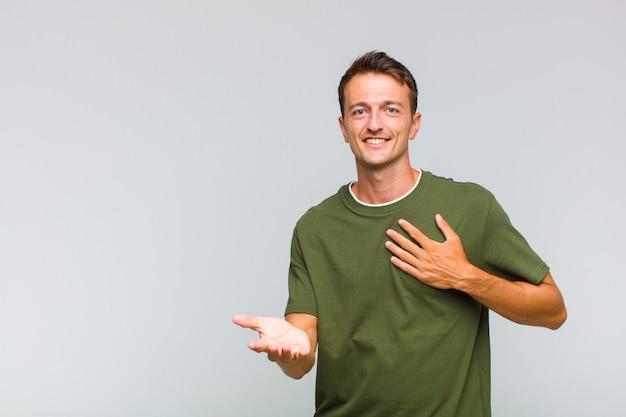 Jonge knappe man die zich gelukkig en verliefd voelt, glimlachend met de ene hand naast het hart en de andere naar voren gestrekt