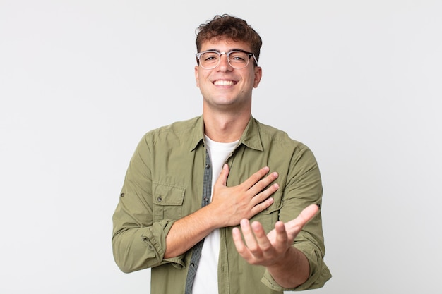 Jonge knappe man die zich gelukkig en verliefd voelt, glimlachend met één hand naast het hart en de andere vooraan gestrekt