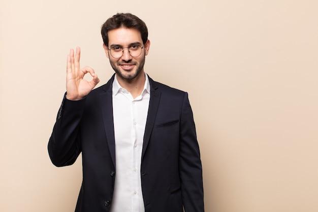Jonge knappe man die zich gelukkig, ontspannen en tevreden voelt, goedkeuring toont met een goed gebaar, glimlachend