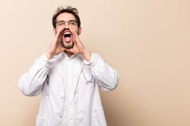 Jonge knappe man die zich gelukkig, opgewonden en positief voelt, een grote schreeuw geeft met handen naast de mond, roept