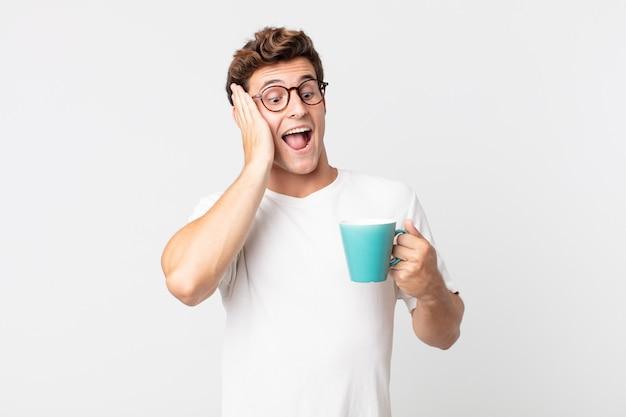 Jonge knappe man die zich gelukkig, opgewonden en verrast voelt en een koffiekopje vasthoudt