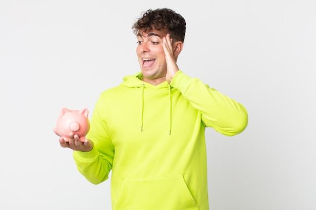 Jonge knappe man die zich gelukkig, opgewonden en verrast voelt en een spaarvarken vasthoudt