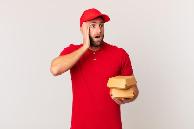 Jonge knappe man die zich gelukkig, opgewonden en verrast voelt hamburger die concept levert