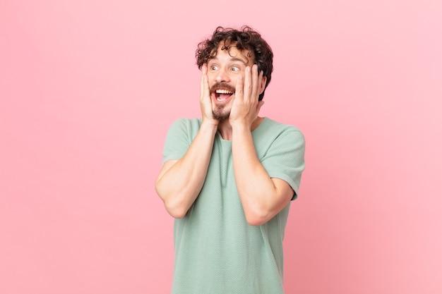 Jonge knappe man die zich gelukkig, opgewonden en verrast voelt