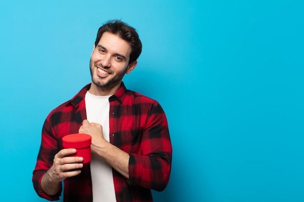 Jonge knappe man die zich gelukkig, positief en succesvol voelt, gemotiveerd wanneer hij voor een uitdaging staat of goede resultaten viert