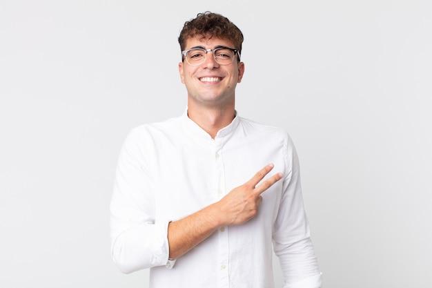 Jonge knappe man die zich gelukkig, positief en succesvol voelt, met de hand die een v-vorm over de borst maakt, overwinning of vrede toont