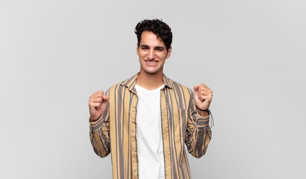 Jonge knappe man die zich gelukkig, positief en succesvol voelt, overwinning, prestaties of veel geluk viert
