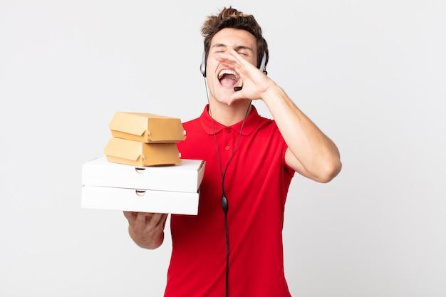 Jonge knappe man die zich gelukkig voelt, een grote schreeuw geeft met de handen naast de mond. afhaal fastfood concept