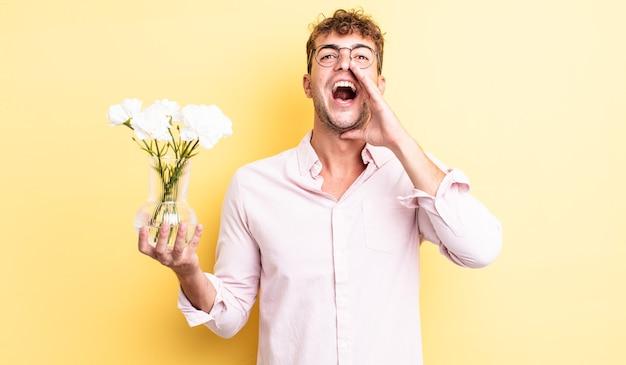 Jonge knappe man die zich gelukkig voelt, een grote schreeuw geeft met de handen naast de mond. bloemen concept