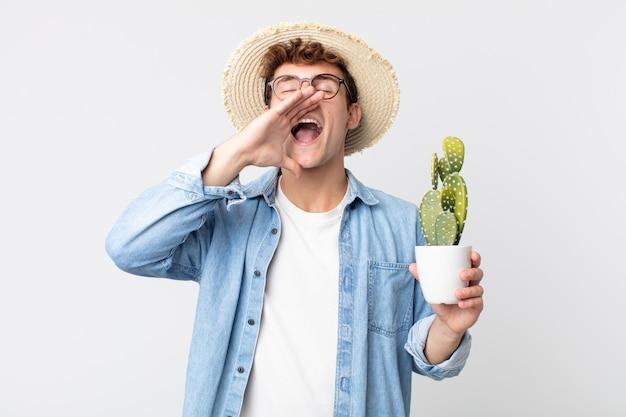 Jonge knappe man die zich gelukkig voelt, een grote schreeuw geeft met de handen naast de mond. boer met een decoratieve cactus