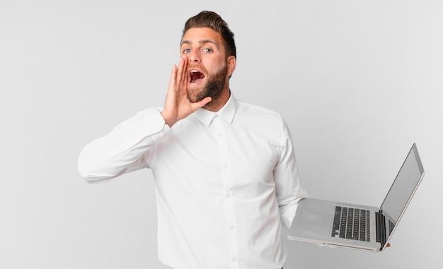 Jonge knappe man die zich gelukkig voelt, een grote schreeuw geeft met de handen naast de mond en een laptop vasthoudt