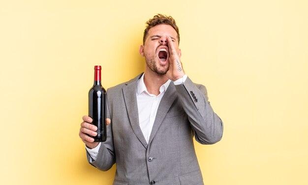 Jonge knappe man die zich gelukkig voelt, een grote schreeuw geeft met de handen naast de mond. fles wijn concept