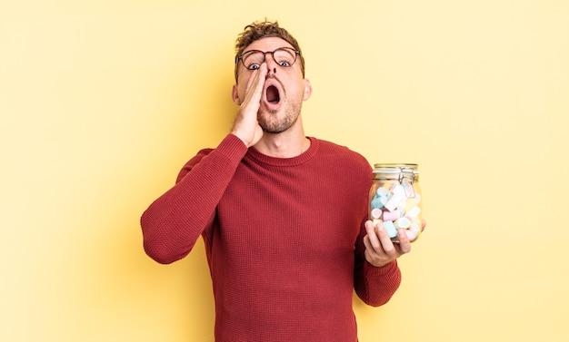 Jonge knappe man die zich gelukkig voelt, een grote schreeuw geeft met de handen naast de mond. gelei snoepjes concept