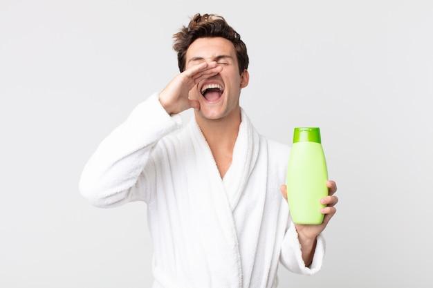 Jonge knappe man die zich gelukkig voelt, een grote schreeuw geeft met de handen naast de mond met een badjas en een shampoofles vasthoudt