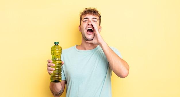 Jonge knappe man die zich gelukkig voelt, een grote schreeuw geeft met de handen naast de mond. olijfolie concept