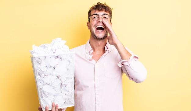 Jonge knappe man die zich gelukkig voelt, een grote schreeuw geeft met de handen naast de mond. papier ballen prullenbak concept