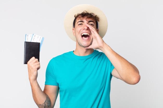 Jonge knappe man die zich gelukkig voelt, een grote schreeuw geeft met de handen naast de mond. reiziger met zijn paspoort