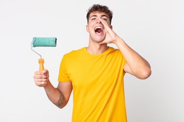 Jonge knappe man die zich gelukkig voelt, een grote schreeuw geeft met de handen naast de mond. schilderij thuis concept