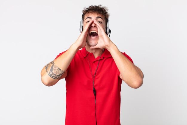 Jonge knappe man die zich gelukkig voelt, een grote schreeuw geeft met de handen naast de mond. telemarketeer concept