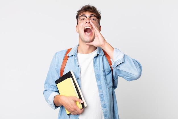 Jonge knappe man die zich gelukkig voelt, een grote schreeuw geeft met de handen naast de mond. universitair studentenconcept