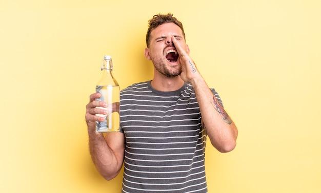Jonge knappe man die zich gelukkig voelt, een grote schreeuw geeft met de handen naast de mond. waterconcept