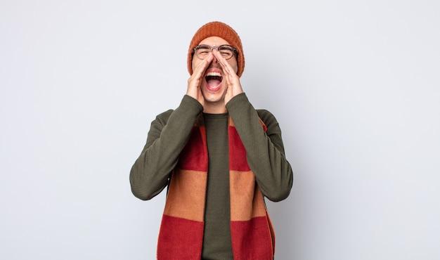 Jonge knappe man die zich gelukkig voelt, een grote schreeuw geeft met de handen naast de mond. winterkleren concept