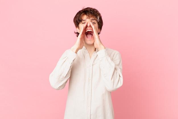 Jonge knappe man die zich gelukkig voelt, een grote schreeuw geeft met de handen naast de mond