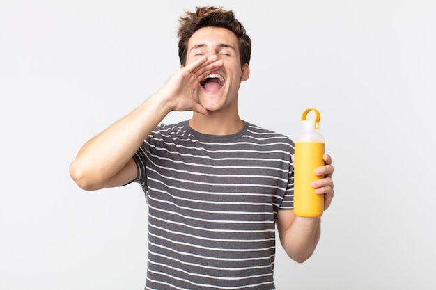 Jonge knappe man die zich gelukkig voelt, een grote schreeuw uitdeelt met de handen naast de mond en een koffiethermoskan vasthoudt