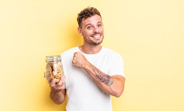 Jonge knappe man die zich gelukkig voelt en een uitdaging aangaat of het concept van de koekjesfles viert
