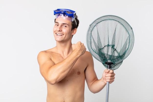 Jonge knappe man die zich gelukkig voelt en een uitdaging aangaat of viert met een bril en een visnet