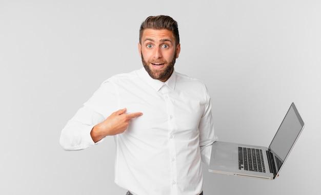 Jonge knappe man die zich gelukkig voelt en naar zichzelf wijst met een opgewonden en een laptop vasthoudt