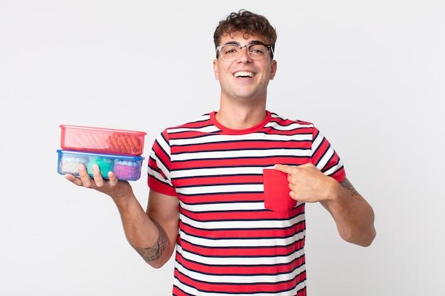 Jonge knappe man die zich gelukkig voelt en naar zichzelf wijst met een opgewonden en een lunchdoos vasthoudt